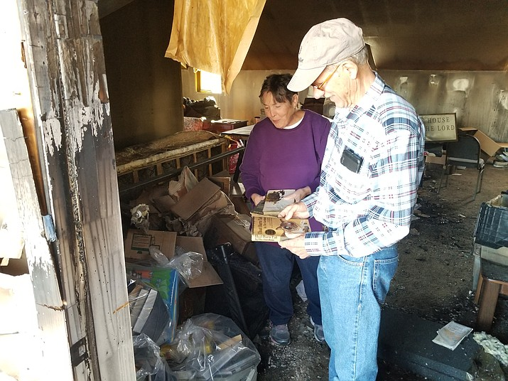 Joe and Kathy Hull look fondly on some books that survived a lightning-caused fire that all but destroyed their home in mid-September, 2019. (Max Efrein/Courier)