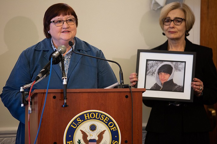 Dorothy Paugh, left, who helped push a red-flag gun law in Maryland, with a picture of her son, Peter, who took his own life with a firearm. Paugh's father also committed suicide with a gun. (Photo by Harrison Mantas/Cronkite News)