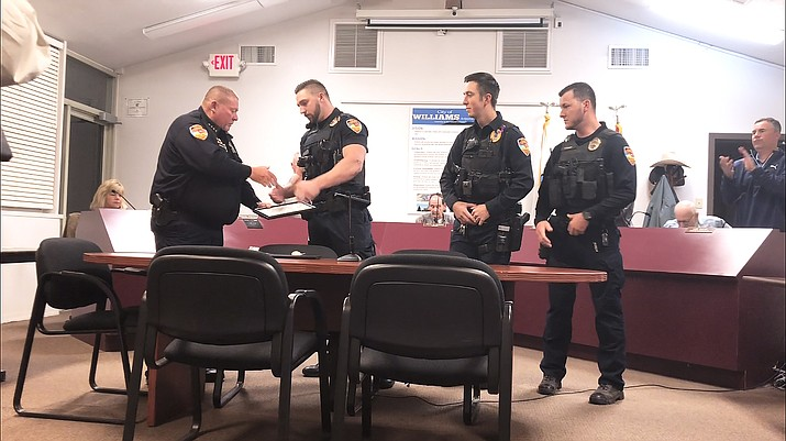 Chief Herman Nixon awards Kohl Nixon, Thomas Sanders and Tyler Forbes for their lifesaving efforts during a 911 call in June. (Wendy Howell/WGCN)
