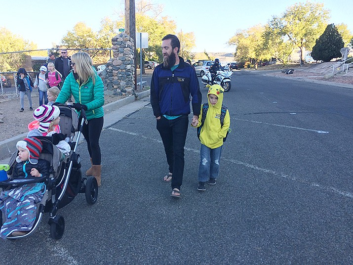 Skyview father and son, Micah Miland and second-grader Israel, proceed on the walk from Ken Lindley toward South Rush Street that required crossing West Gurley Street. (Nanci Hutson/Courier)