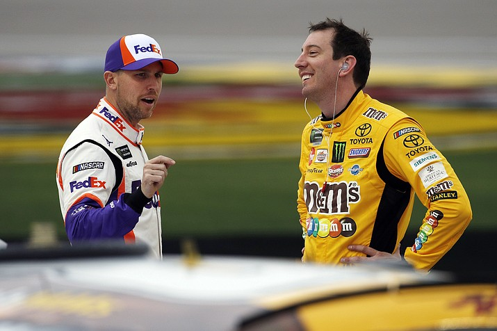 In this March 1, 2019, file photo, drivers Denny Hamlin, left, and Kyle Busch talk in pit lane before qualifying for the NASCAR Cup Series auto race at Las Vegas Motor Speedway in Las Vegas. Hamlin has all the momentum headed into the third round of NASCAR's playoffs, which start Sunday at Martinsville Speedway. But hot on his bumper are his Joe Gibbs Racing teammates, regular season champion Kyle Busch and Martin Truex Jr., who leads the series with six wins this season. (John Locher/NASCAR, file)