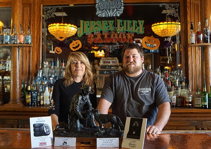 Susan Roberts and Josh Makrauer show the prizes available in this year's annual Friends of Jersey Lilly Fundraiser for the Courthouse Lighting. Along with a bronze sculpture donated by local artist Bradford Williams, the drawing will feature a rose gold diamond pendant donated by Raskin's Jewelers and a set of new tires from Prescott Tire Pros. (Cindy Barks/Courier)