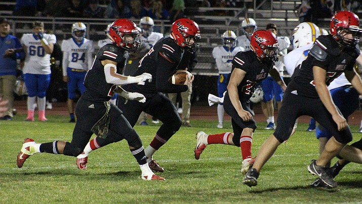 Lee Williams junior Levi Beckham, center, runs the ball as Donnie Simms, left, and Wesley Boyd block for him during a 48-7 loss to Prescott on Friday. (Photo by Beau Bearden/Daily Miner)