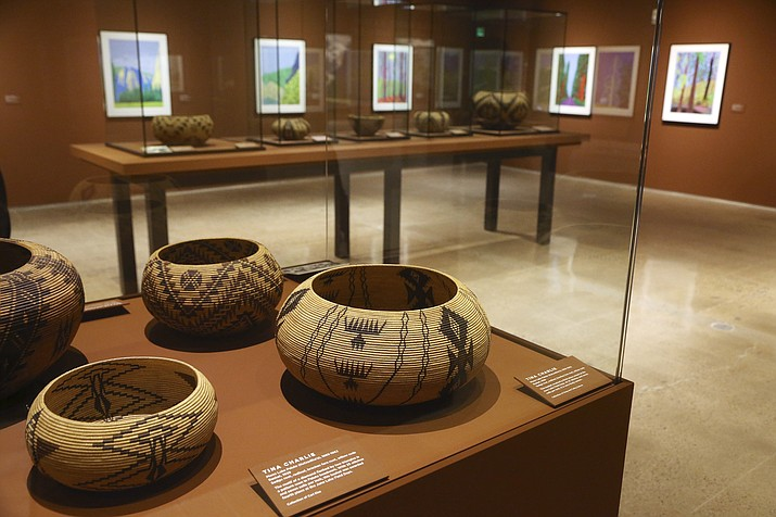 """In this Wednesday, Oct. 23, 2019, photo, British artist David Hockney has his Yosemite work, background, along with baskets from weavers of the Miwok and Mono Lake Paiute tribes on display at the Heard Museum in Phoenix. """"David Hockney's Yosemite and Masters of California Basketry"""" exhibition opens Monday. (Ross D. Franklin/AP)"""