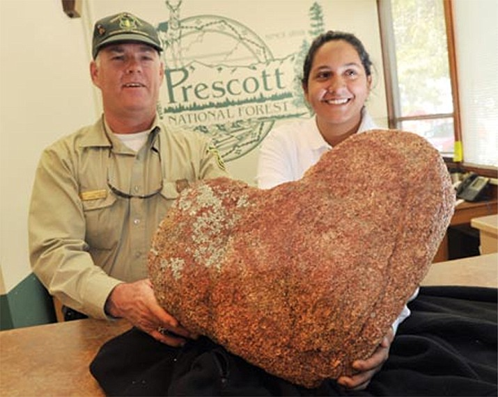 """Prescott National Forest compliance officer Gary Lowrie and student temporary employment program member Dana Torrico hold up the """"heart rock"""" that a man anonymously returned to the forest's offices on Monday. (Les Stukenberg/The Daily Courier)"""