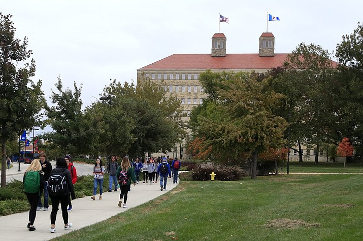 In this Oct. 24, 2019, file photo students walks in front of Fraser Hall on the University of Kansas campus in Lawrence, Kan. Americans collectively owe nearly $1.5 trillion in student loans, more than twice the total a decade ago. It's a burden that weighs on millions of adults, shaping their life choices and often stunting their financial growth. (AP Photo/Orlin Wagner, File)