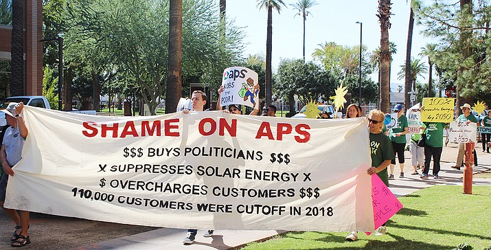About 30 protesters marched around the Arizona Corporation Commission building in Phoenix before an early September meeting on APS shutoff policy. (Photo by Jake Eldridge/Cronkite News)