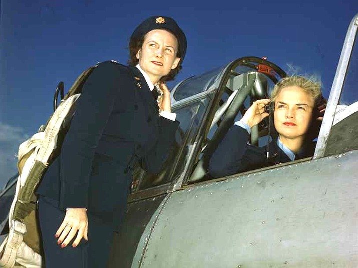 "WASP Ann McClellan adjusts her earphones in the cockpit of a BT-13 while Anne Johnson stands on the wing of the plane."" Credit:  Image 4A-22688-K3615, Record group 342, National Archives and Records Administration at College Park, College Park, Maryland."
