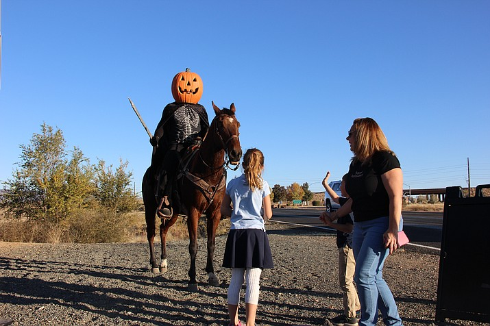 The Massimo family visits with the Headless Horseman outside the entrance to Pronghorn Ranch in Prescott Valley Thursday, Oct. 31, 2019. (Max Efrein/Courier)