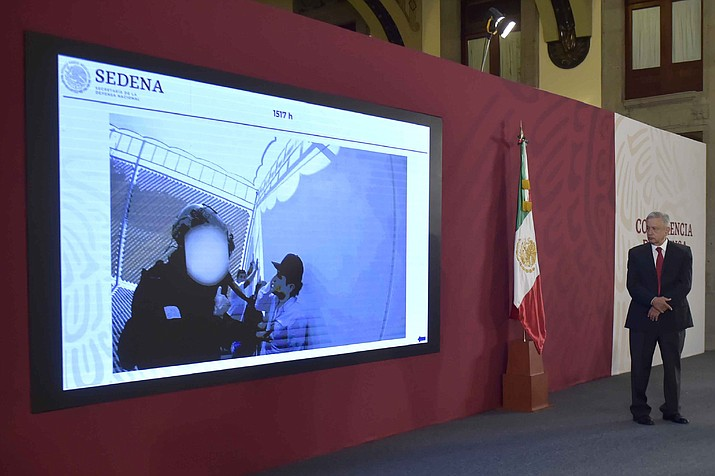 """In this handout photo provided by Mexico's Presidential Press Office, President Andres Manuel Lopez Obrador watches a video that shows the capture of Ovidio Guzman Lopez, a son of Joaquin """"El Chapo"""" Guzman, who was then released, during the daily press conference at the National Palace in Mexico City, Wednesday, Oct. 30, 2019. Lopez Obrador said on Thursday that his government will not be forced into a drug war, adding that his strategy is something else. """"Nothing has hurt Mexico more than the dishonesty of the governing,"""" Mexico's president said, implying that corruption is to blame for the country's insecurity, violence and drug trafficking. (Mexico's Presidential Press Office via AP)"""