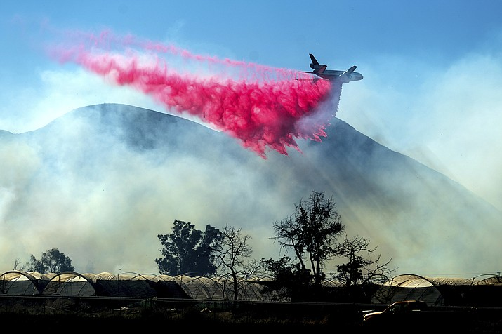 An air tanker drops retardant as the Maria Fire approaches Santa Paula, Calif., on Friday, Nov. 1, 2019. According to Ventura County Fire Department, the blaze has scorched more than 8,000 acres and destroyed at least two structures. (Noah Berger/AP)