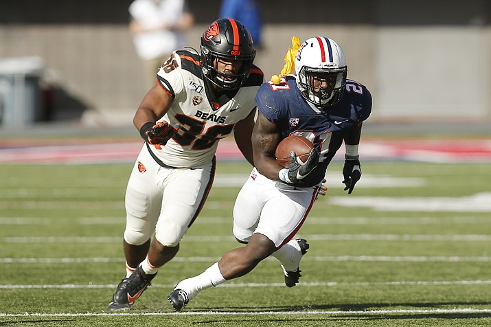 Arizona's J.J. Taylor (21) runs away from Oregon State linebacker Omar Speights (36) as a referee's' flag hits him in the shoulder pads in the first half during a football game, Saturday, Nov. 2, 2019, in Tucson. (Rick Scuteri/AP)