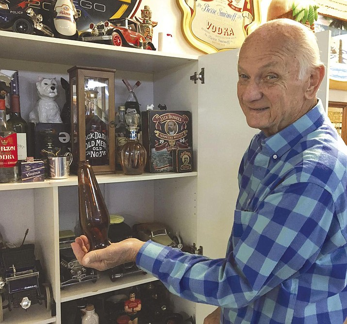 Gerry Tieri of Lake Havasu City holds a 45-year-old Coors beer bottle. Tieri worked for liquor distributors and amassed a large collection of alcohol promotional items. (Photo by Pam Ashley/Today's News-Herald)