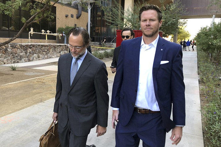Maricopa County Assessor Paul Petersen, right, along with his attorney, Kurt Altman, leave after Petersen's arraignment hearing in Phoenix, Tuesday, Nov. 5, 2019. Petersen pleaded not guilty to fraud and theft charges stemming from an alleged human smuggling scheme involving pregnant women from the Marshall Islands who were brought to the U.S. to give birth for adoptions. (AP Photo/Jacques Billeaud)