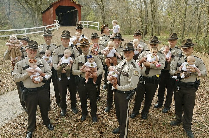 In this Nov. 4, 2019, photo fourteen Jefferson County Sheriffs Deputies pose for a photo with their babies at the Sandy Creek Covered Bridge in Jefferson County, Mo. They are from left, with their babies: Adam Lambrich with Lilliana; AJ Kausler with Lucy; Matt Moore with Luca; Scott Ehrhard with Hudson; Andy Sides with Carter; Greg Bohn with Evelyn; Dustin Isenhart with Kash; Nick Gamm with Gweneth; Colby McCreary with Sawyer; Cody Cawvey with Micah; Shawn Loness with Connor; Andrew Griffon with Kinsley; Kevin Karl with Kade; and Roger Waeckerle with Wyatt. (J.B. Forbes/St. Louis Post-Dispatch via AP)