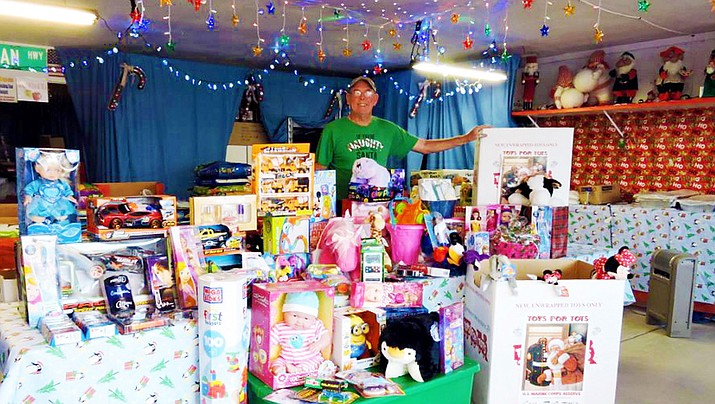 Each year the Mohave County Toys for Tots program collects a mountain of toys for distribution to needy children. Above, Butch Meriwether stands with 116 toys and $343 that he and his wife, Chris Marie, collected for Toys for Tots at their Christmas display in Golden Valley during a prior holiday season. (Courtesy photo)