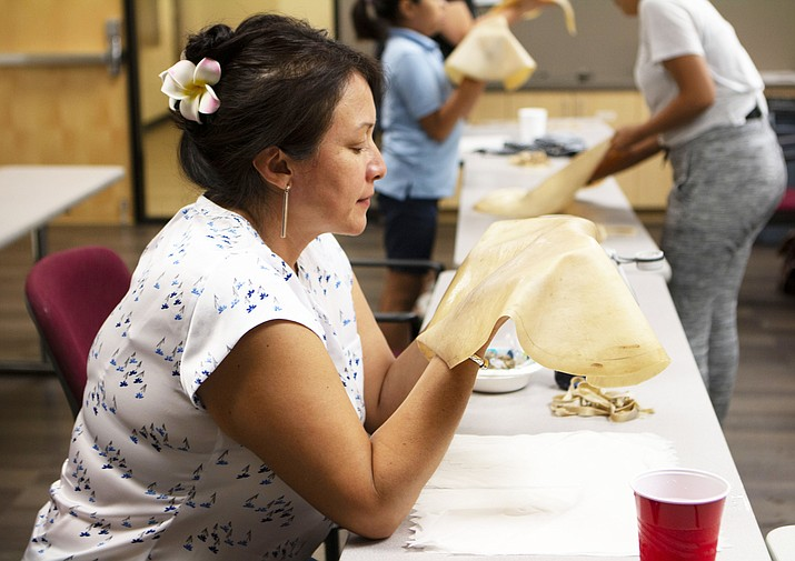 Sheila Lopez blesses the elk hide that will be used to make a hand drum at an Indigenous Art Series event put on by Native Health in Phoenix. (Photo by Annika Tomlin/Cronkite News)