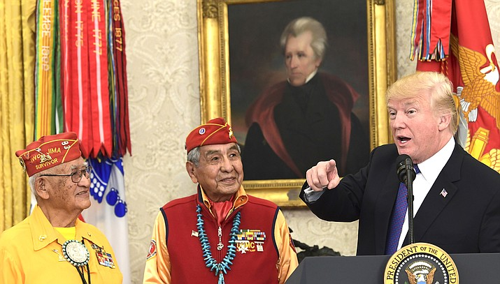 President Donald Trump, right, speaks during a meeting with Navajo Code Talkers including Thomas Begay, left, and Peter MacDonald, center, in the Oval Office of the White House in Washington Nov. 27, 2017. Trump has declared November as a time to celebrate both Native American heritage and the country's founders, a move that upset Native Americans who have historically had the month to themselves to mark their contributions to the nation. (AP Photo/Susan Walsh)