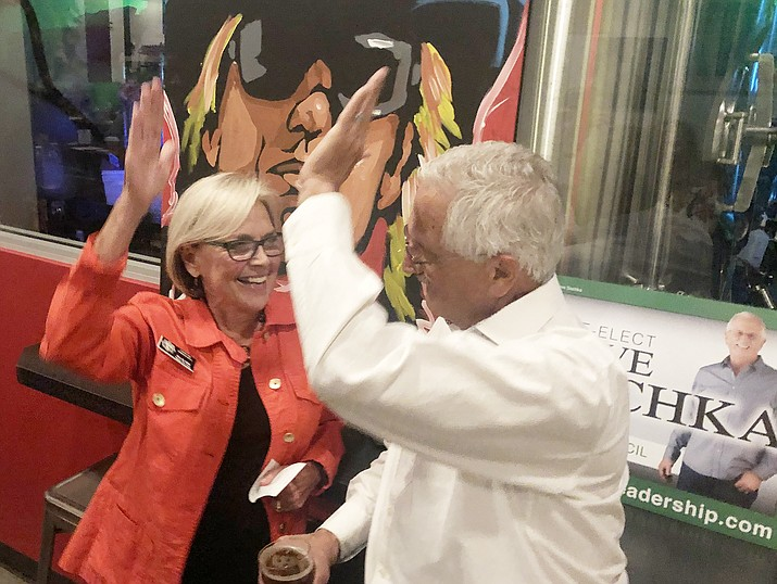 Prescott Mayor Pro Tem Billie Orr and City Councilman Steve Sischka high-five Tuesday night, Nov. 5, 2019, after hearing the unofficial results that indicated that Sischka had won a second, four-year council term. Orr and Sischka were among dozens who turned out for an after-election gathering at the Lazy G Brewhouse in Prescott. (Cindy Barks/Courier)