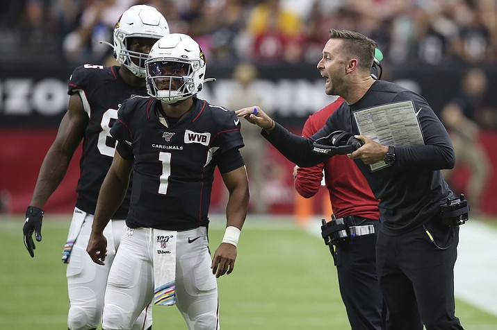 In this Sunday, Oct. 13, 2019, photo, Arizona Cardinals head coach Kliff Kingsbury talks with quarterback Kyler Murray (1) during the first half of a game against the Atlanta Falcons, in Glendale, Ariz. Being a rookie head coach in the NFL is challenging enough, and also calling plays for the offense only increases the difficulty. Murray has helped ease the growing pains for Kingsbury. (Ross D. Franklin/AP, File)