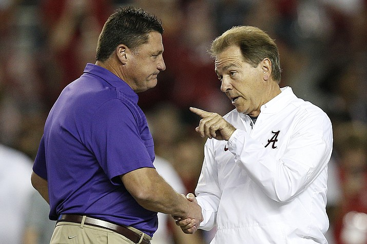 In this Nov. 4, 2017, photo, LSU head coach Ed Orgeron, left, and Alabama head coach Nick Saban meet in the center of the field before a game, in Tuscaloosa, Ala. For the first time in college football history, there will be two games matching teams of at least 8-0 on the same day, according to ESPN Facts and Info. (Brynn Anderson/AP, file)