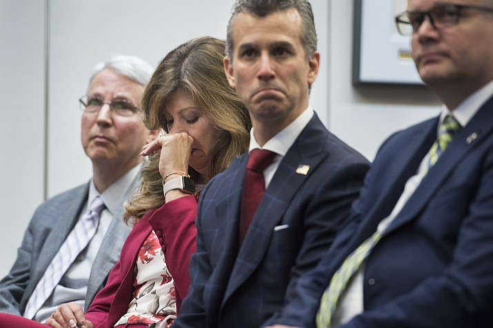 Susan Payne, founder and executive director of Safe2Tell wipes tears, as Peter Langman, left, Max Schachter, who lost his son Alex during the Parkland school mass shooting, center, and Ryan Petty, right, who lost his daughter Alaina during the Parkland school mass shooting, appear at the the release of the Secret Service National Threat Assessment Center's Protecting America's Schools report, in Washington, Thursday, Nov. 7, 2019. The report examines 41-targeted attacks that occurred in schools between 2008 and 2017. (AP Photo/Cliff Owen)