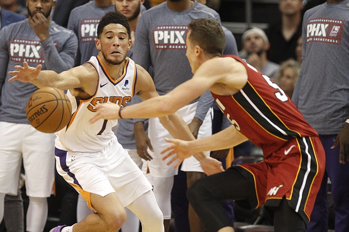 Phoenix Suns' Devin Booker (1) steals the ball from Miami Heat's Duncan Robinson (55) during the second half of a game Thursday, Nov. 7, 2019, in Phoenix. (Darryl Webb/AP)