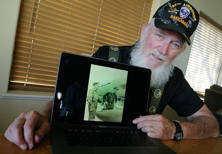 Camp Verde resident Mike Martin looks at a photograph of he and his father, both serving their country in Vietnam, on a laptop computer. Martin has been able to share his Vietnam experience with both his father and his son, Russ. VVN/Bill Helm