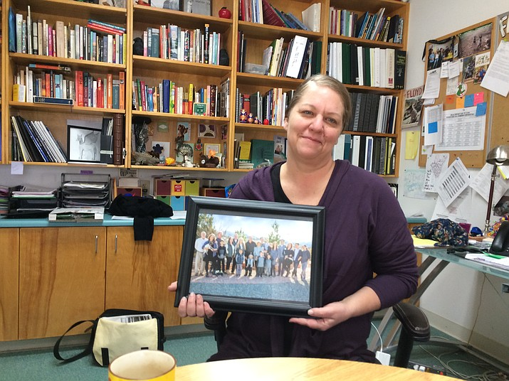 "Melissa Wagoner poses with a photograph of her extended family in the office of her ""second family"" at Northpoint. (Nanci Hutson/Courier)"