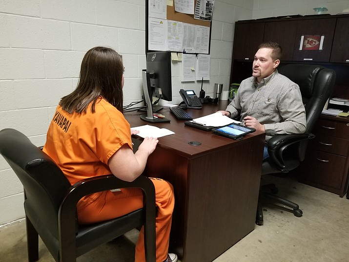 Derek Oltersdorf, an inmate release coordinator at the Yavapai County jail, speaks with a fellow employee posing as an inmate at the jail to demonstrate what Reach Out Program interactions look like during the booking process. (Max Efrein/Courier)
