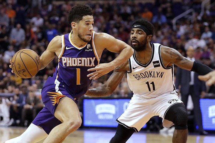 Phoenix Suns guard Devin Booker (1) drives past Brooklyn Nets guard Kyrie Irving (11) during the first half of an NBA basketball game Sunday, Nov. 10, 2019, in Phoenix. (AP Photo/Matt York)
