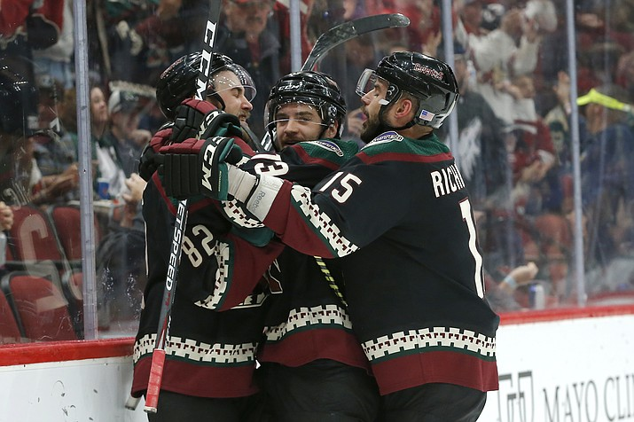 Arizona Coyotes center Vinnie Hinostroza, center, celebrates with Jordan Oesterle (82) and Brad Richardson (15) in the second period during an NHL hockey game against the Minnesota Wild, Saturday, Nov. 9, 2019, in Glendale. On Tuesday, the Coyotes signed general manager John Chayka to a long-term contract extension. (Rick Scuteri/AP)