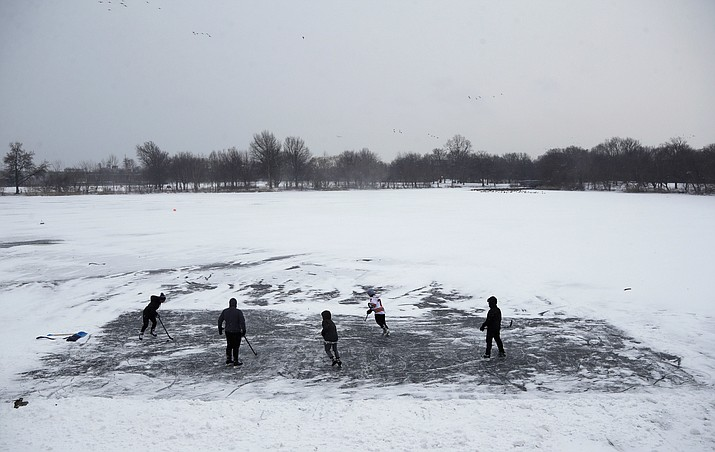 In this Thursday, Jan. 4, 2018 file photo, youths play ice hockey on a frozen pond at Philadelphia's Franklin Delano Roosevelt Park during a winter storm. New concussion guidance shows there isn't enough solid evidence to answer some of parents' most burning questions about contact sports. That includes what age is safest to start playing them. (Matt Slocum/AP, file)
