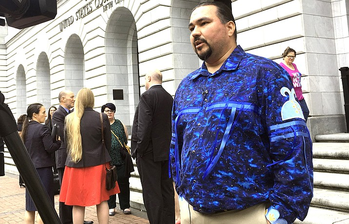 Tehassi Hill, tribal chairman of the Oneida Nation, stands outside a federal appeals court in New Orleans, following arguments on the constitutionality of a 1978 law giving Native American families preference in adoption of Native American children. (AP Photo/Kevin McGill, File)