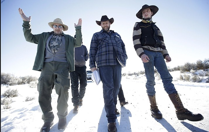 Steve Atkins, left, talks with Ammon Bundy, center, one of the sons of Nevada rancher Cliven Bundy, following a news conference at Malheur National Wildlife Refuge near Burns, Oregon in 2016. (Rick Bowmer/Associated Press)