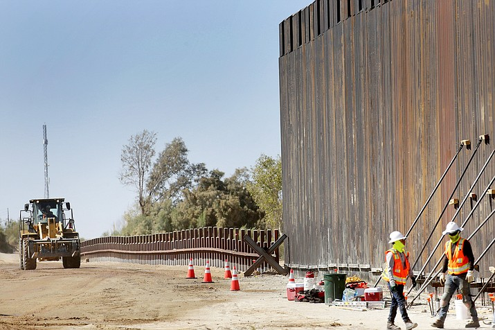 Government contractors erect a section of Pentagon-funded border wall along the Colorado River Sept. 10 in Yuma, Ariz. A federal appeals court hears arguments against diverting Pentagon money for border wall construction as time runs out. It says the Trump administration has moved quickly to spend the money after the Supreme Court rejected an emergency appeal to prevent work from starting in July. (AP Photo/Matt York,File)