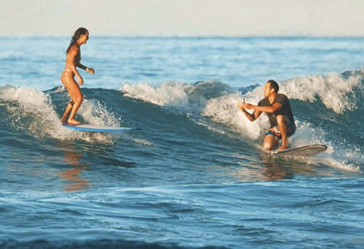 In this Sunday, Nov. 10, 2019 photo, instead of just hanging ten when surfing with his girlfriend, Chris Garth drops to one knee and proposes to Lauren Oiye in the surf off Queen's Beach in Waikiki in Honolulu. Hawaii News Now reported that Lauren Oiye said yes just before Chris Garth dropped the ring in the ocean. Luckily, he had a spare. Garth said he knew it could go wrong, so he used a stand-in while they were out in the water. The real ring was on shore at Queen's Beach, where the two met years before. (Tommy Pierucki via AP)