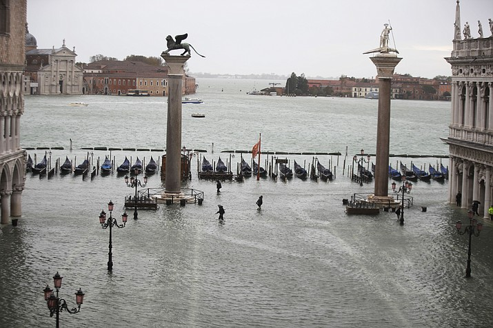 People make their way in a flooded St. Mark's Square in Venice, Italy, Friday, Nov. 15, 2019. Waters are rising in Venice where the tide is reaching exceptional levels just three days after the Italian lagoon city experienced its worst flooding in more than 50 years. (Luca Bruno/AP)