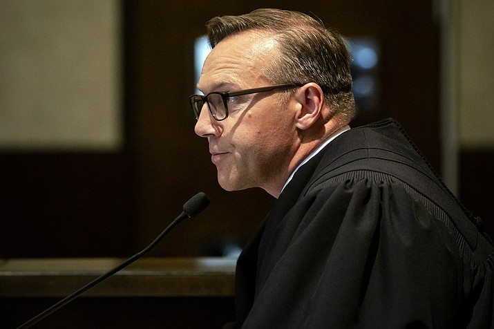 In this Aug. 26, 2019 photo, Judge Thad Balkman reads a summary of his decision in the opioid trial at the Cleveland County Courthouse in Norman, Okla. Judge Balkman reduces amount Johnson & Johnson must pay state to help clean up opioid crisis by $107 million to $465 million on Friday Nov. 15, 2019. (Chris Landsberger/The Oklahoman via AP, Pool)