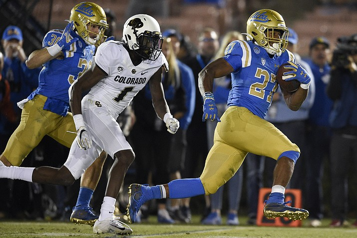 UCLA running back Joshua Kelley, right, runs for a touchdown past Colorado cornerback Delrick Abrams Jr., center, during the second half of a game as Ethan Fernea follows the play in Los Angeles, Saturday, Nov. 2, 2019. UCLA won 31-14. (Kelvin Kuo/AP)