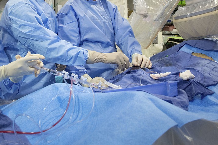 In this Feb. 16, 2017 file photo, surgeons perform a non-emergency angioplasty at Mount Sinai Hospital in New York. Through a blood vessel in the groin, a tube is guided to a blockage in the heart. A tiny balloon is then inflated to flatten the clog, and a mesh tube called a stent is inserted to prop the artery open. According to a federally funded study released on Saturday, Nov. 16, 2019, people with severe but stable heart disease from clogged arteries may have less chest pain if they get a procedure to improve blood flow rather than just giving medicines a chance to help, but it won't cut their risk of having a heart attack or dying over the following few years. (AP Photo/Mark Lennihan)