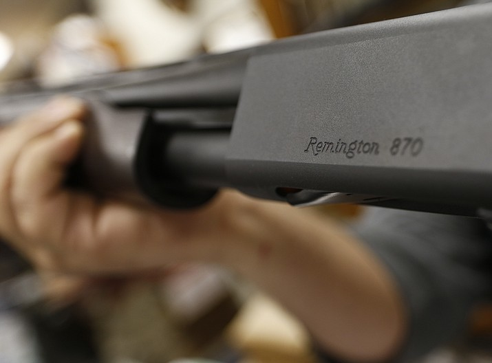 In this March 1, 2018 photo, the Remington name is seen etched on a model 870 shotgun at Duke's Sport Shop in New Castle, Pa. For years, the gun industry has been immune from most lawsuits, but a recent ruling allowing families of victims in the Newton school shooting to challenge the way an AR-15 used by the shooter was marketed is upending that longstanding roadblock. The U.S. Supreme Court recently rejected efforts by gunmaker Remington to quash the lawsuit, allowing it to continue to be heard in Connecticut courts. (Keith Srakocic/AP, File)