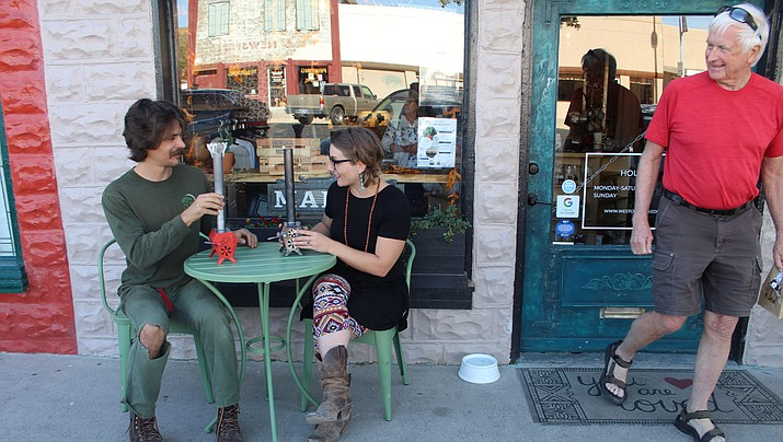 """Alex Lemelin and Sarah Ferry talk in downtown Kingman on Friday, Nov. 15, two weeks before Shop Small Saturday. Lemelin's original """"little hottie wood stoves"""" will be available for purchase at West of Third, 224 E Beale St., which Ferry co-owns. (Photo by Agata Popeda/Daily Miner)"""