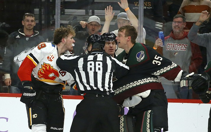 Linesman Tyson Baker (88) tries to break up Calgary Flames left wing Matthew Tkachuk, left, and Arizona Coyotes goaltender Darcy Kuemper (35) during a brawl during the second period of an game, Saturday, Nov. 16, 2019, in Glendale. (Ross D. Franklin/AP)