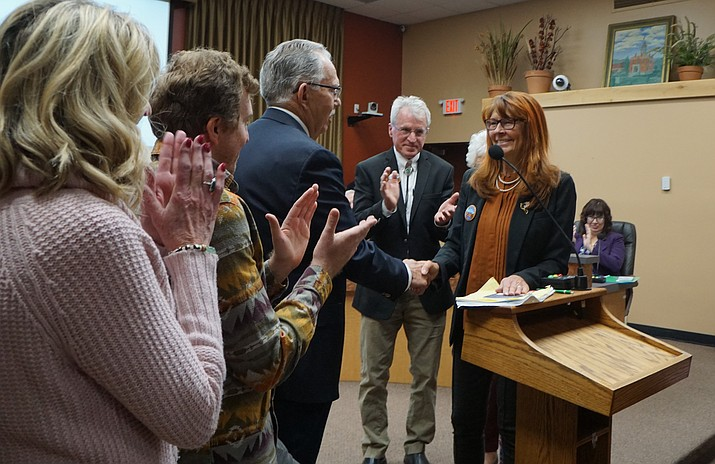 Newly sworn-in Councilwoman Cathey Rusing, right, shakes hands with City Councilman Phil Goode, who administered the oath of office, while Rusing's husband Tom, second from right, and other family members look on. Rusing was the top vote-getter in the city's August primary. She was elected to a four-year term. (Cindy Barks/Courier)
