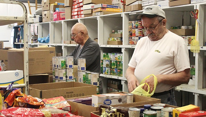 Local grocery donations are processed by food bank volunteers Fred Steffen (left) and Brad Guy. (Photo by Agata Popeda/Miner)