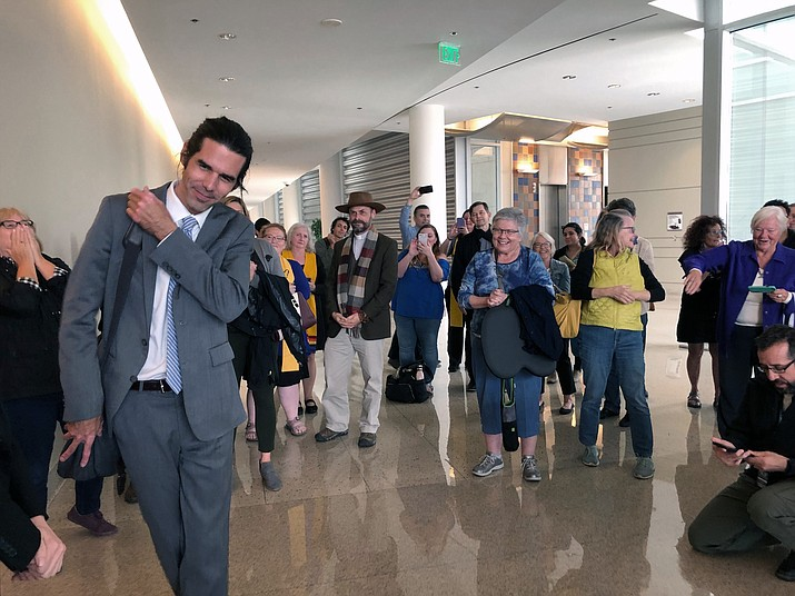 Scott Warren, left, of Ajo, Ariz., thanks his supporters and attorneys after walking out of court in Tucson, Ariz. on Wednesday, Nov. 20, 2019, after being acquitted of two counts of harboring in a case that garnered international attention. Prosecutors said Warren illegally helped two migrants avoid authorities. He said he was fulfilling his humanitarian duties by helping two injured men. (Astrid Galvan/AP)