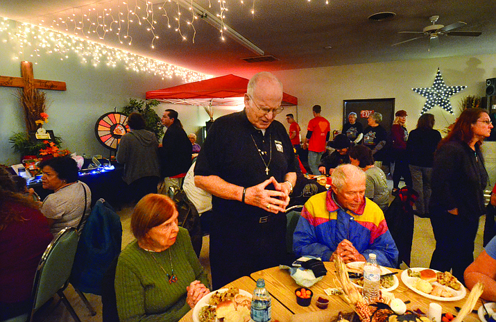 Pastor Bill Witt said a prayer at each of the tables Wednesday as part of Old Town Mission's annual community meal.