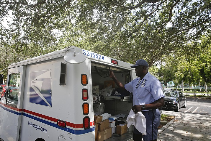 In this June 14, 2018, file photo, Elston Bradshaw, a mail carrier for the United States Postal Service closes a mail truck door after delivering mail to an apartment complex in Aventura, Fla. People tend to spend a lot of time planning their holiday travel but not a lot preparing for their return home. Have your mail and subscriptions placed on hold so things don't accumulate at your front door, tipping off potential thieves that you're away. (Brynn Anderson/AP, file)