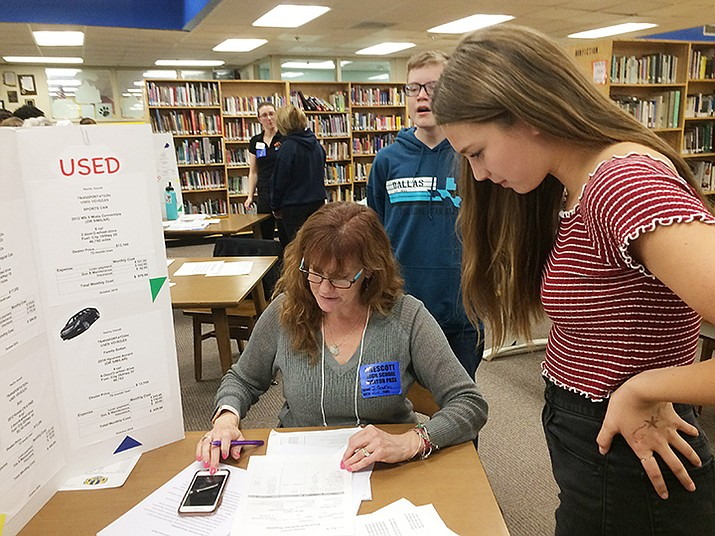 Freshman Ava Hlavacheck reviews car purchases with AAUW member Jennifer Bradley. (Nanci Hutson/Courier)
